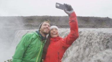 Couple taking selfie by Dettifoss waterfall — Stock Video