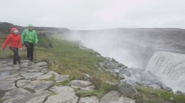 Tourist couple walking by Dettifoss waterfall — Stock Video