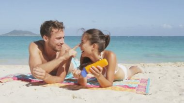 Couple putting sunscreen lotion on beach — Stock Video