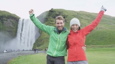 People cheering by Skogafoss waterfall — Stock Video