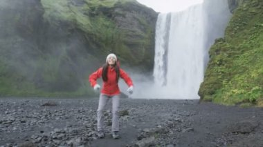 Girl jumping by waterfall on Iceland — Stock Video