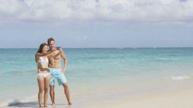 Couple taking selfie on beach using smartphone — Stock Video
