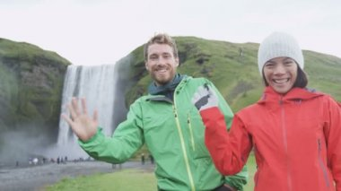 People waving hello with hand by Skogafoss — Stock Video