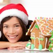 Woman in santa hat and gingerbread house — Stock Photo #69710655