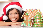 Woman in santa hat and gingerbread house — Stock Photo