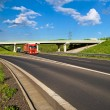 Bridge over an empty highway in the countryside, under a bridge passing two trucks — Stock Photo #52919825
