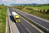 Corridor highway with the transition for wildlife, the highway goes yellow truck — Stock Photo