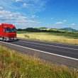 Rural landscape with road you are driving a red truck — Stock Photo #63109941