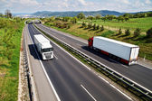 Corridor highway with the transition for animals, going down the highway two trucks — Stock Photo