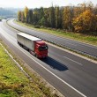 The highway between deciduous forests with leaves in fall colors, the highway ride three trucks — Stock Photo #65015399