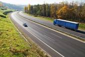 The highway between deciduous forests with leaves in fall colors, the highway goes blue truck and a passenger car — Stock Photo
