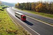 The highway between deciduous forests with leaves in fall colors, the highway ride three trucks — Stock Photo