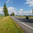 An empty road lined with poplar alley in the countryside, passing motorcycle — Stock Photo #65570153