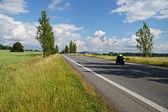 An empty road lined with poplar alley in the countryside, passing motorcycle — Stock Photo