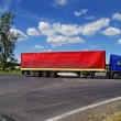 Blue truck with red sail passing a crossroads in the countryside — Stock Photo #65936201