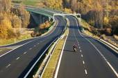 Empty highway leading across the bridge over the valley, motorcycle, electronic toll gates — Stock Photo