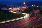 The city with street lighting in the valley at night, the light path headlights of cars — Stock Photo