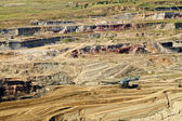 Bunk wall surface mine with exposed colored minerals and brown coal, the pit mining equipment — Stock Photo