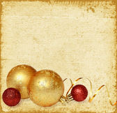 Yellow and red balls with golden ribbon — Stock Photo