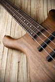 Bass guitar on aged wood — Stock fotografie