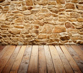 Stone wall with wooden floor — Stock Photo