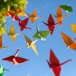 Colorful origami birds flying. Sky background. — Stock Photo #70973749