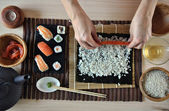 Hands cooking sushi — Stock Photo