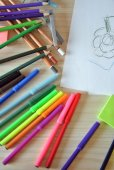 Desk full of crayons, paints and drawing paper — Stock Photo