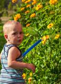 Baby is watering the flowers — Stock Photo