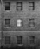 Black and white photo of brick facade with windows — Stock Photo