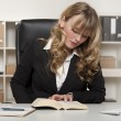 Young businesswoman reading a book at work — Stock Photo #52605765