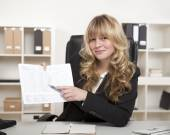 Smiling businesswoman pointing to a spreadsheet — Photo