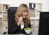 Businesswoman having a quick snack at her desk — Stock Photo