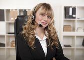 Friendly businesswoman wearing a headset — Stock Photo