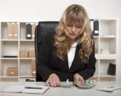 Businesswoman counting out money at her desk — Stock Photo