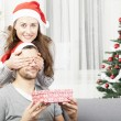 Girls makes her boyfriend a christmas gift — Stock Photo #55711075