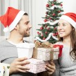 Couple giving christmas presents — Stock Photo #55711143