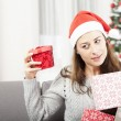 Young girl shaking christmas gift — Stock Photo #55711221