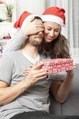 Girl suprise boyfriend with christmas gift — Stock Photo