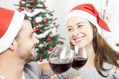 Couple enjoy chistmas with wine on sofa — Stock Photo