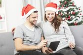 Happy couple look on tablet pc for christmas — Stock Photo