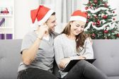 Happy couple makes a wish list for christmas — Stock Photo