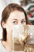 Girl hide behind christmas present box — Stockfoto
