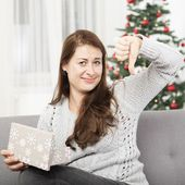 Girl is unhappy about christmas gift and thumb down — Stock Photo