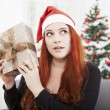 Girl is shaking happy christmas present — Stock Photo #55862177