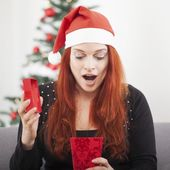 Girl is suprised open christmas present — Stock Photo