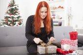 Happy girl wrap christmas present boxes — Stock Photo