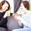 Two happy female friends with coffee cups — Stock Photo #65250189