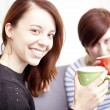 Two happy female friends with coffee cups — Stock Photo #65250227