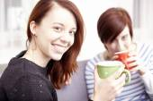 Two happy female friends with coffee cups — Stock Photo